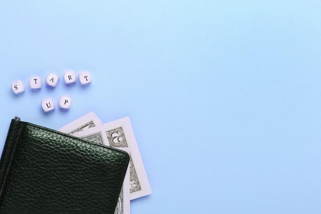 Sluit omhoog van zwarte portefeuille op een blauwe achtergrond met het woorden opstarten van houten brieven. bovenaanzicht, minimalisme