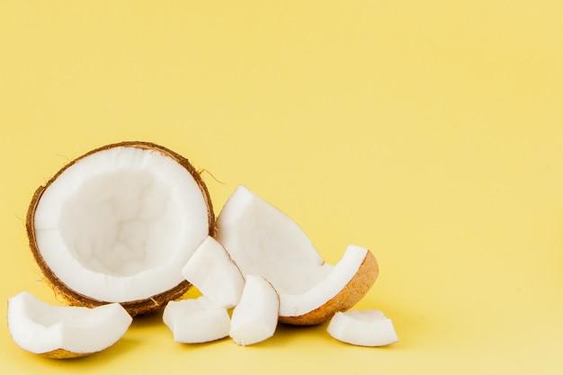 Sluit omhoog verse kokosnotenstukken die op geel worden geïsoleerd
