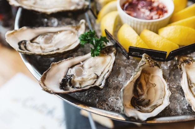 Sluit omhoog verse oesters en veel soorten verse die oesters in rond dienblad met plakcitroen en kruidige saus worden gediend.