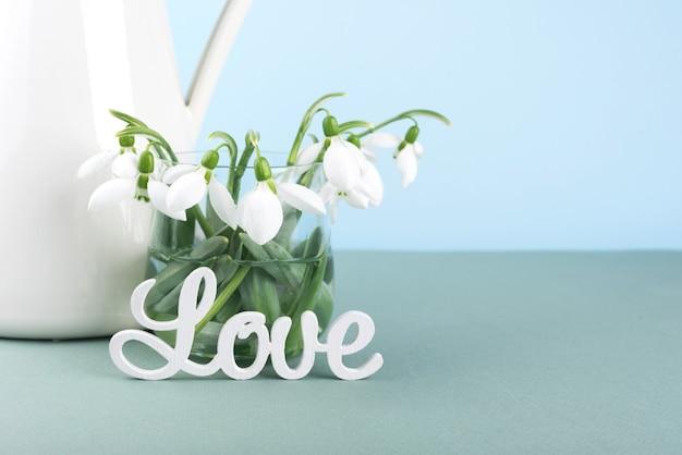 Sluit omhoog verse sneeuwklokjes in een glasvaas en liefdetekst
