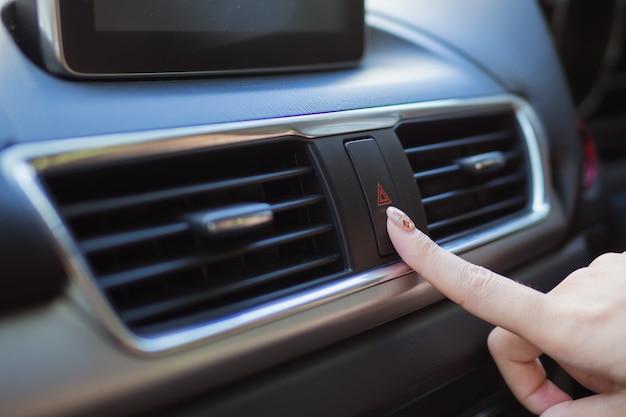 Sluit omhoog vinger die de lichte bodem van de autonoodsituatie in auto raken