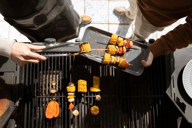 Sluit omhoog vrienden die barbecue maken