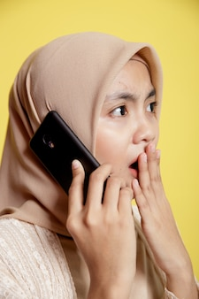 Sluit omhoog vrouw die een hijab draagt die een telefoon met geschokte uitdrukking gebruikt die op gele muur wordt geïsoleerd