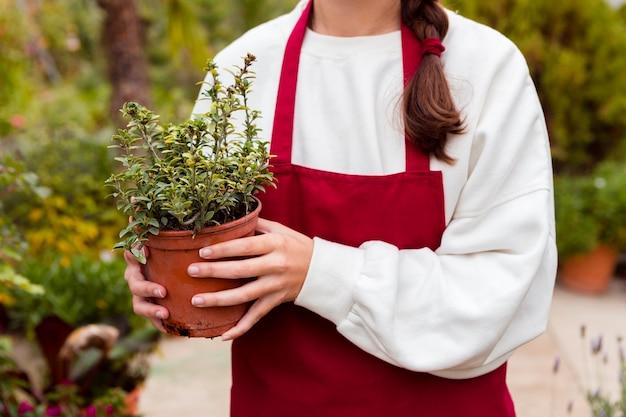 Sluit omhoog vrouw die in het tuinieren kleren pot houden