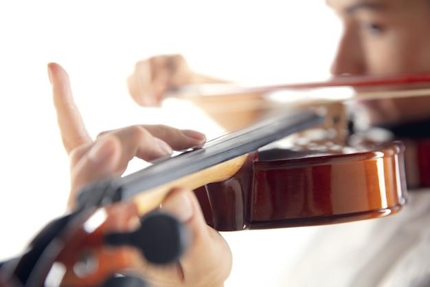 Sluit omhoog vrouw die viool speelt die op witte studioachtergrond wordt geïsoleerd. geïnspireerde muzikant, details van kunstbezetting, wereldklassiek instrument. concept van hobby, creativiteit, inspiratie.