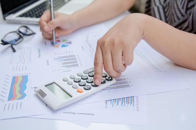 Sluit omhoog vrouw gebruikend calculator op document grafiekgegevens met het doen van financiën op kantoor.