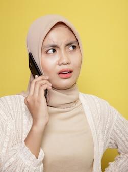 Sluit omhoog vrouw hijab met een oproepende telefoonuitdrukking die op gele achtergrond wordt geïsoleerd