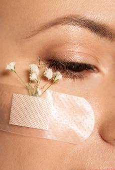 Sluit omhoog vrouw met de bloem van de bandhulp op gezicht