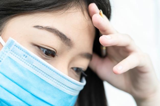 Sluit omhoog vrouw met hoofdpijn dragend masker voor bescherming