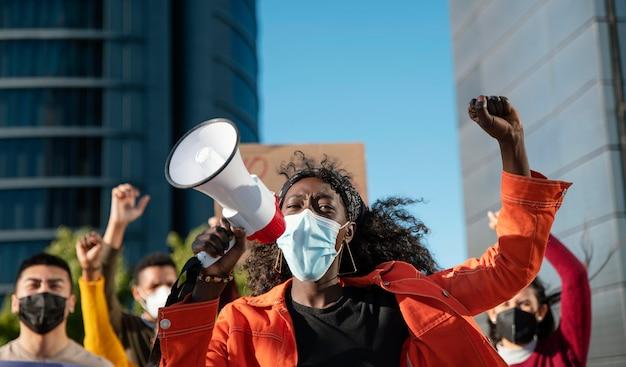 Sluit omhoog vrouw met megafoon die masker draagt