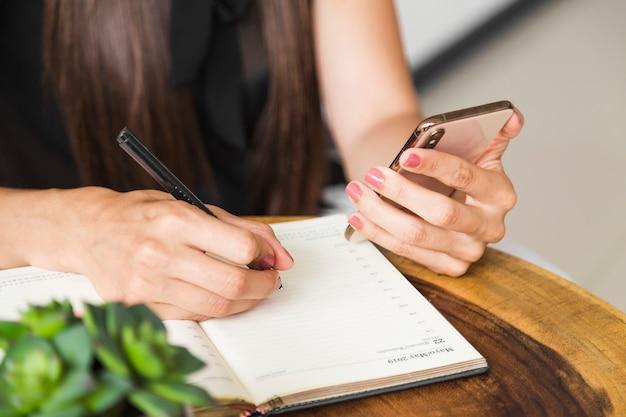 Sluit omhoog vrouw schrijvend van telefoon