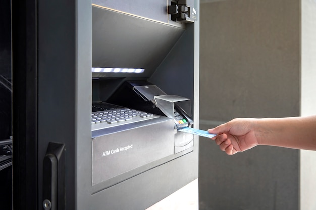 Sluit omhoog vrouwelijke hand die creditcardbank van atm-machine met behulp van om geld op te nemen