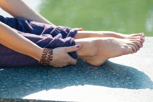 Sluit omhoog vrouwelijke handen houdend de voetzitting stelt