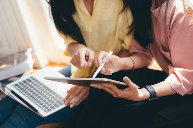 Sluit omhoog vrouwen samen gebruikend online mobiel gadget