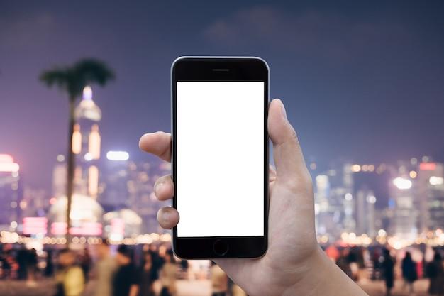 Sluit omhoog vrouwenhand die een slimme telefoon met het lege scherm met behulp van bij winkelcomplex.