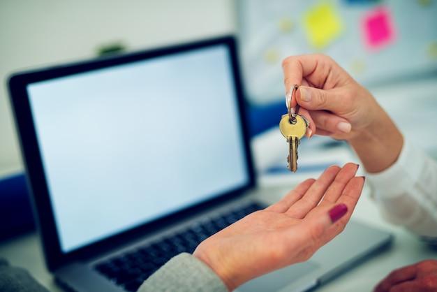 Sluit omhoog vrouwenhand die sleutels van het appartement geeft aan nieuwe vrouweneigenaar.