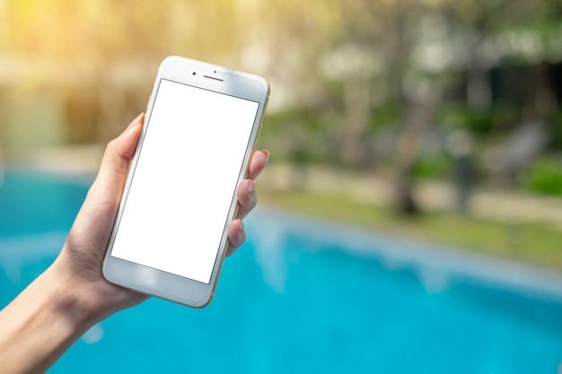 Sluit omhoog vrouwenhand houdend witte telefoon op het lege scherm bij insi van de park openlucht het knippen weg
