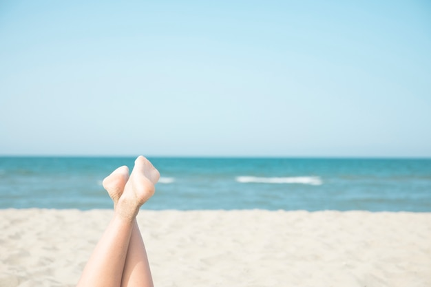 Sluit omhoog vrouwenvoeten bij de kust