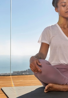 Sluit omhoog vrouwenzitting op yogamat