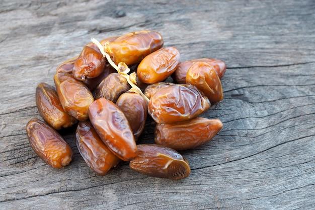 Sluit omhoog vruchten van dadelpalm op oude houten lijst