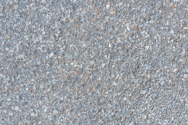 Sluit omhoog wegdek met kiezelsteen op de concrete achtergrond van de vloertextuur