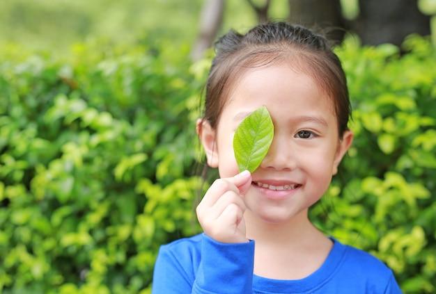 Sluit omhoog weinig aziatisch kindmeisje die een groen blad houden die juist oog op groene tuinachtergrond sluiten.