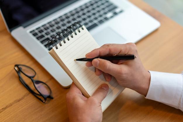 Sluit omhoog werknemer schrijvend in blocnote