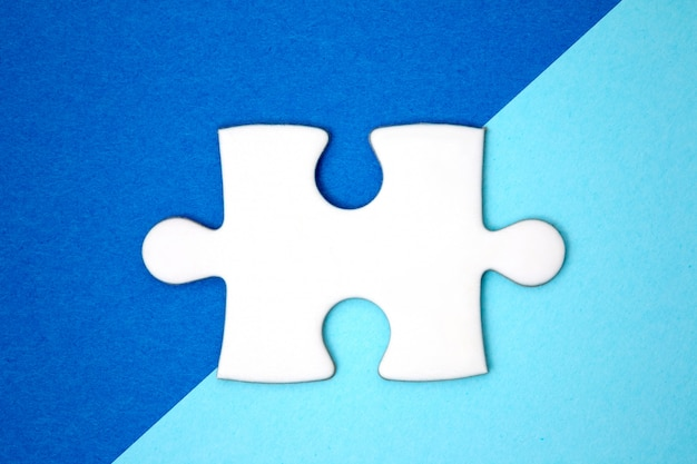 Sluit omhoog wit raadselstuk over een meetkunde blauwe achtergrond. minimale stijl. plat leggen.