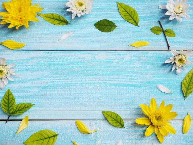 Sluit omhoog witte en gele chrysantenbloemen op blauwe houten kaderachtergrond