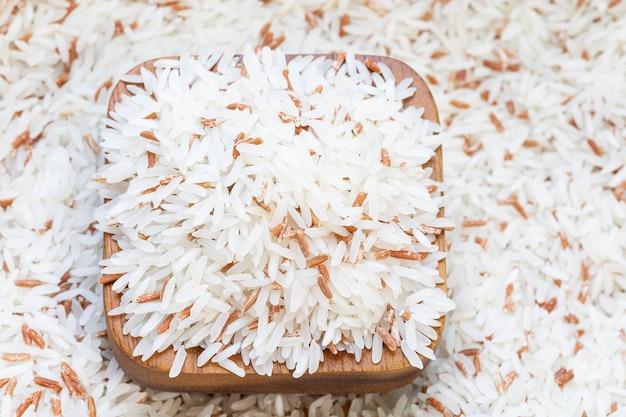 Sluit omhoog witte rijstmix met rode rijst in een houten kop op rijstachtergrond.