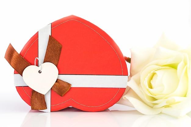 Sluit omhoog witte roze en hart gevormde doos op wit