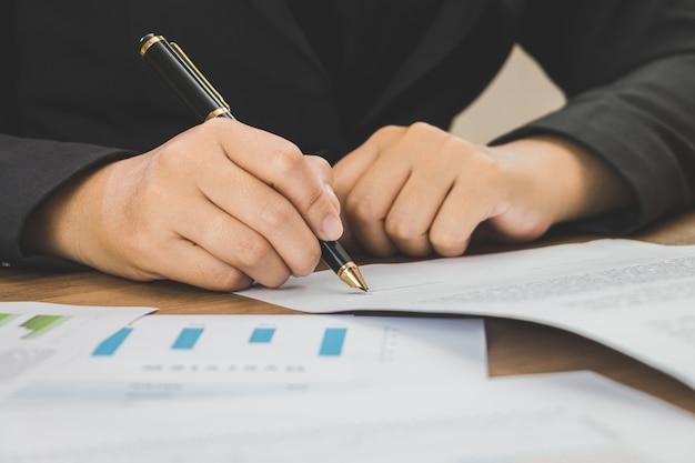 Sluit omhoog zakenman die termijnen van overeenkomstendocumenten ondertekenen op zijn bureau, die concept ondertekenen