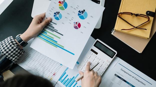 Sluit omhoog zakenman gebruikend calculator en laptop voor het berekenen van financiën, belasting, boekhouding, statistieken en analytisch onderzoeksconcept