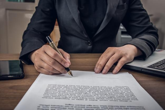 Sluit omhoog zakenman ondertekeningsvoorwaarden en overeenkomstendocument op zijn bureau in het bureau