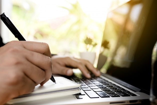 Sluit omhoog zakenmanhand die aan laptop computer aan houten bureau werken