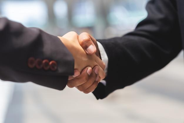 Sluit omhoog zakenmanmens en onderneemsterhanddruk voor partner, bedrijfsconcept.