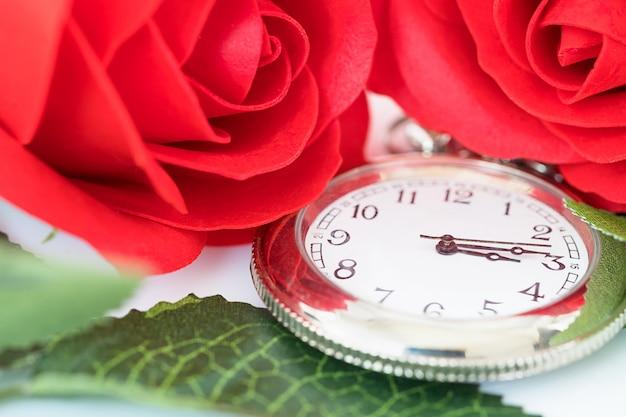 Sluit omhoog zakhorloge en rode rozenbloem