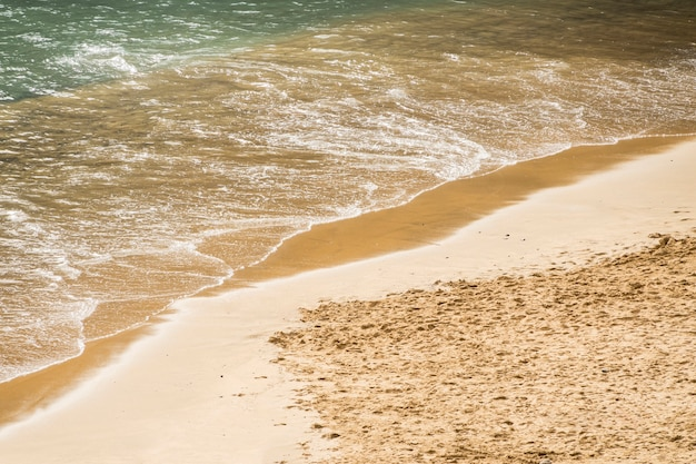 Sluit omhoog zeewater wat betreft zand bij de kust