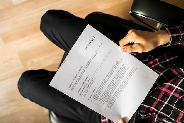 Sluit omhoog zittende zakenman zoekend contractdetails in leunstoel g