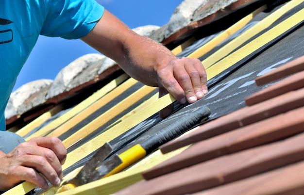Sluit op de handen van een arbeider die e-dak van een huis vernieuwt