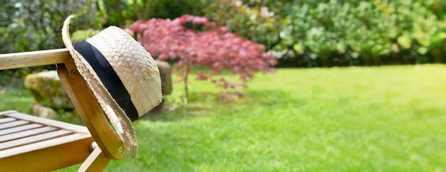 Sluit op een strohoed op een armleuning van een stoel in een tuin in de zomer