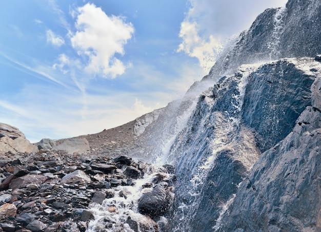 Sluit op water dat van gletsjer op een rotsachtige muur in alpiene berg stroomt