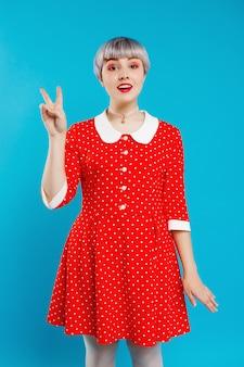 Sluit portret mooi popachtig meisje met kort licht violet haar die rode kleding dragen die overwinningsgebaar over blauwe muur tonen