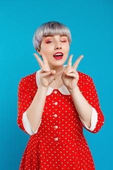 Sluit portret mooi popachtig meisje met kort licht violet haar die rood dresswinking dragen die overwinningsgebaar over blauwe muur tonen