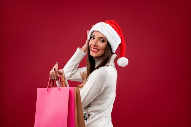Sluit portret omhoog mooie kaukasische vrouw in rode kerstmanhoed op rode muur. kerst nieuwjaar concept. leuke vrouwentanden die positieve emoties met het winkelen zak glimlachen.