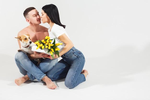 Sluit portret omhoog zitten het jonge paar en koesterend, houdend gele bloemen en hond in studio op witte achtergrond. paar omarmen met dromerige amoureuze uitdrukking. liefdevolle familie. vrouwendag vieren.