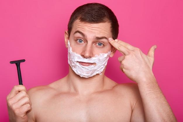 Sluit portret van de knappe mens met het scheren van schuim op gezicht, houdt scheermes ter beschikking klaar voor het scheren