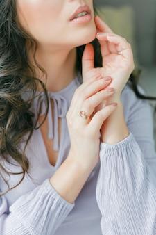 Sluit portret van een jonge mooie krullende vrouw in een lila jurk