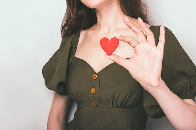 Sluit portret van een verliefd meisje met een hart van papier op haar borst