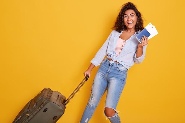 Sluit portret van europees caucaiaans wijfje gekleed in modieuze kleren draagt koffer met vliegtuigtickets en documenten, dromend over vlucht en reis, geïsoleerd over gele achtergrond.